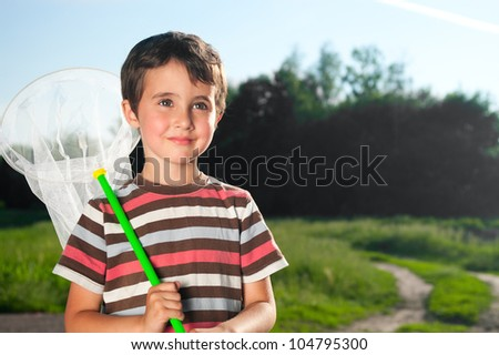 Little boy with hoop net outdoors on the forest meadow in summer