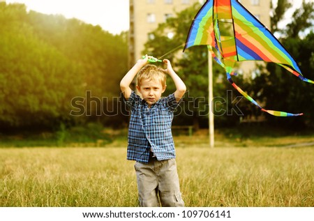 Little boy with kite flying over his head
