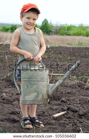 Little boy with old watering can on field