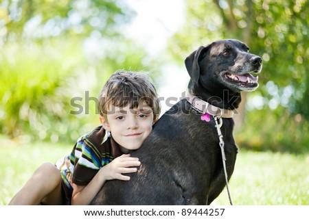 Little boy with pet labrador retriever dog