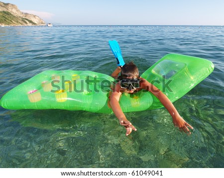 little boy with scuba diving mask and flippers swimming on green pool raft