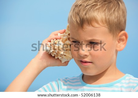 little boy with shell listening noise of sea. focus on left eye.