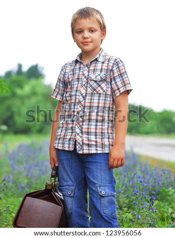 Little boy with suitcase standing about road