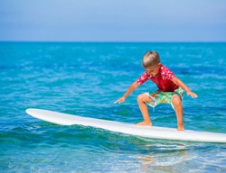 Little boy with surf board learning surfing