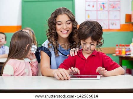 Little boy with teacher using digital tablet in kindergarten
