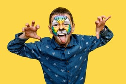 Little boy with tiger faceart or aquagrim posing isolated on yellow background.