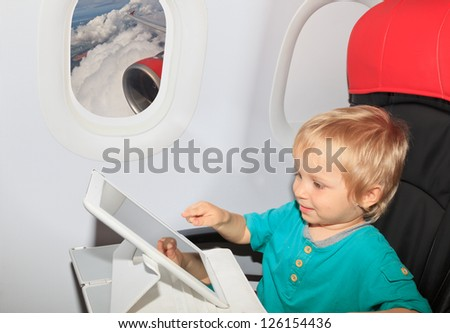 little boy with touch pad on plane in flight