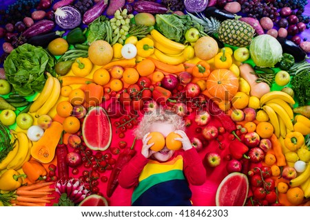 Little boy with variety of fruit and vegetable. Colorful rainbow of raw fresh fruits and vegetables. Child eating healthy snack. Vegetarian nutrition for kids. Vitamins for children. View from above.