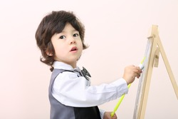 Little boy with yellow pointer draws with chalk on chalkboard in studio.
