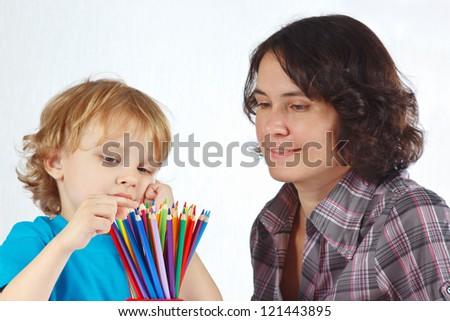 Little boy with young mother looks on color pencils on a white background