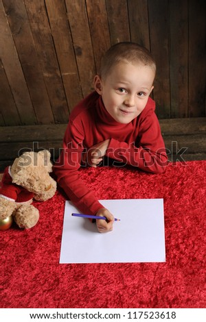 little boy writing a letter for Santa, weathered wooden background