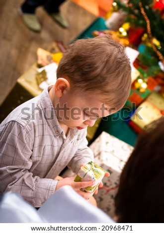 Little boy ( 3 years ) getting present at Christmas Eve.