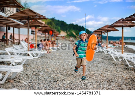little Boy 6 years old hat with inflatable orange circle runs along beach during the summer holidays. Happy child on holiday by the sea learn to swim the water. Family vacation travel on vacation.