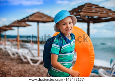 little Boy 6 years old hat with inflatable orange circle runs along beach during the summer holidays. Happy child on holiday by the sea learn to swim the water. Family vacation travel on vacation. #1454781374