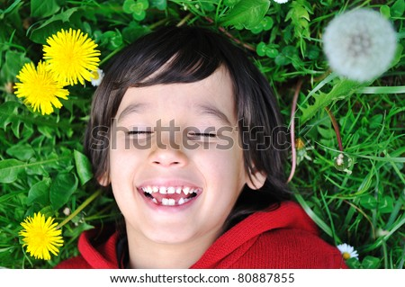 Little boy, 7 years old, in nature, on green meadow - stock photo