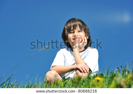 Little boy, 7 years old, in nature, on green meadow