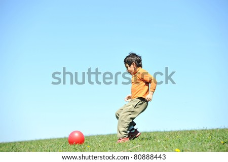 Little boy, 7 years old, in nature, playing with ball alone on green meadow