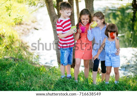 Little boys and girl is drinking red juice sitting on nature background. Happy children drinking juice.