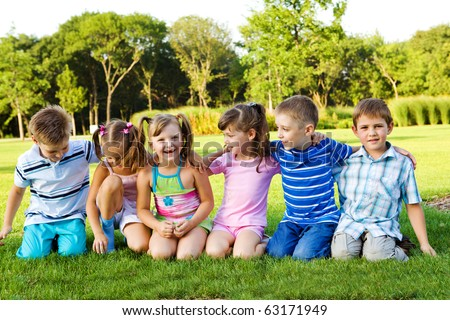Little boys and girls sitting on grass and embracing