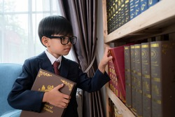 Little boys in suit looking and choose book in shelf.