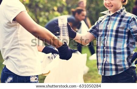Little Boys Picking Up Plastic Bottle in The Park Volunteer Community Service #631050284