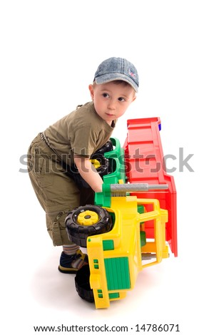 Little boys play with toy truck over white background with light shadows. Boy turn over the car