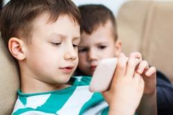 Little boys playing on smartphone, indoor