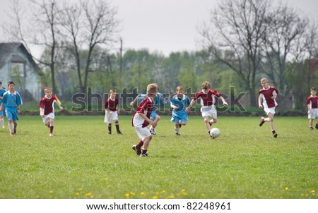 Little Boys  playing soccer on the sports field
