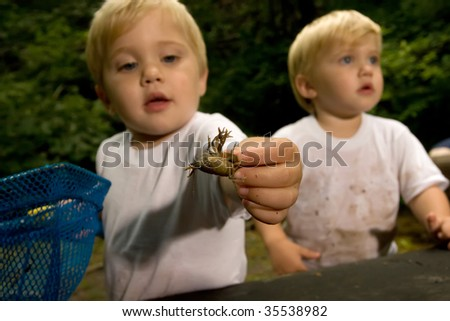 little boys playing with a crawfish