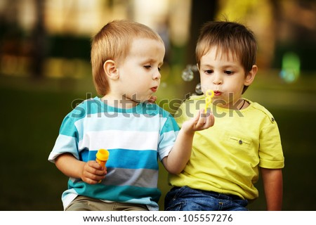 little boys playing with bubbles - stock photo