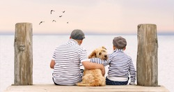 little boys sitting with dog on the shore of Lake, children hugging their dog