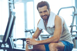 Little break. Handsome young men in sportswear holding water bottle and looking at camera with smile while sitting at gym