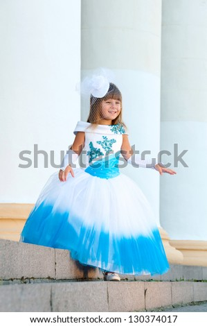 Little bride. A girl in a lush white and blue wedding dress and hat with netting