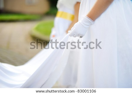 Little bridesmaids holding bride's wedding dress - stock photo