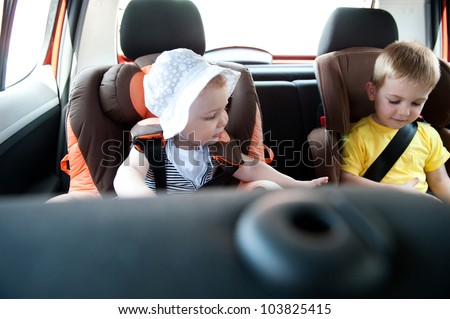Little brother and his baby sister traveling in baby car seats