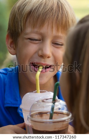 Little brother and sister drinking milkshakes in a cafe outdoors