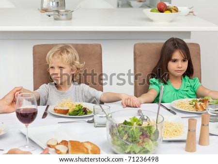 Little brother and sister holding their hands while praying at lunch in the kitchen