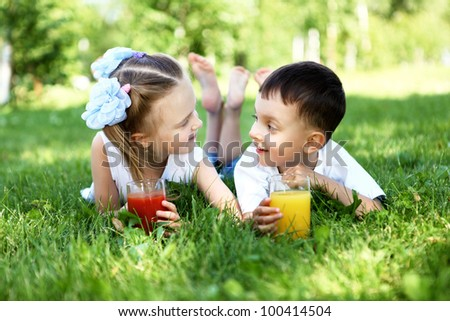 Little brother and sister lying on the grass together in summer park