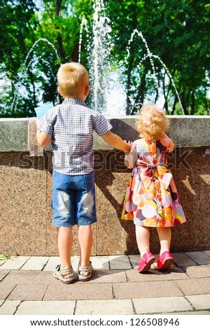 Little brother and sister on toes looking at fountain