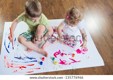 Little brother and sister painting on floor. View from above.