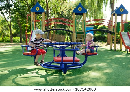 Little brother and sister spinning on roundabout at playground