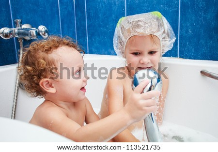 little brother and sister taking a relaxing bath with foam