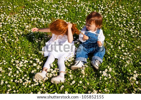 Little brother sitting on the grass and pulling sisters hair