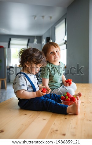Little brothers eat strawberries are sitting on a wooden table in the kitchen. Foto stock ©