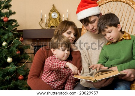 Little brothers pointing at page of book while their father reading it to them