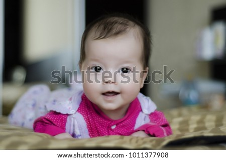 little brown eyed baby in pink pajamas lying on the bed #1011377908