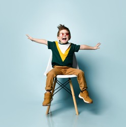 Little brunet male in sunglasses, colorful t-shirt, brown pants, sneakers. Spread hands like flying, screaming, sitting on white chair against blue background. Childhood, fashion. Close up, copy space