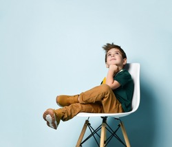 Little brunette boy in a colorful T-shirt, brown pants and sneakers. The boy looks up, propping his chin with his fist, sitting on a white chair on a blue studio background. Childhood, fashion.
