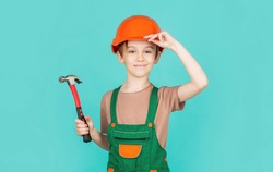 Little builder in helmet and hummer. Child dressed as a workman builder. little boy wearing helmet. Portrait little builder in hardhats hammer. Child building helmet, hard hat. Hammer hammering.