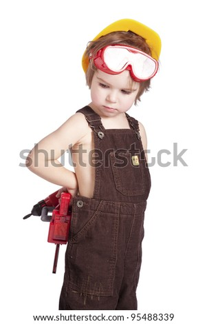 little builder in the helmet, goggles and overalls with a drill and saw the work of thinking about the future